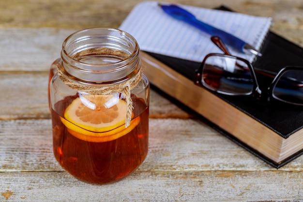 Buch, stift, gläser und tee mit zitrone auf dem tisch