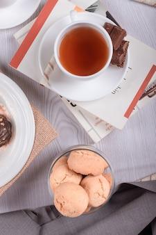 Buch, süße snacks und eine tasse tee auf dem tisch