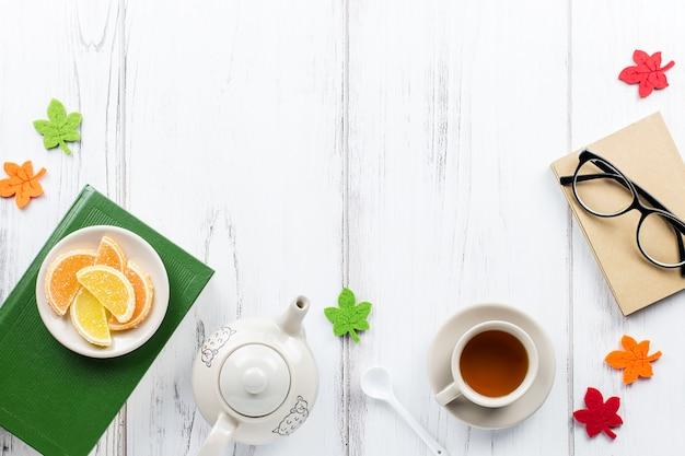 Buch, tasse tee, teekanne, bonbons und gläser, flachgelegt. gemütlicher hintergrund, lesekonzept. kopieren sie platz