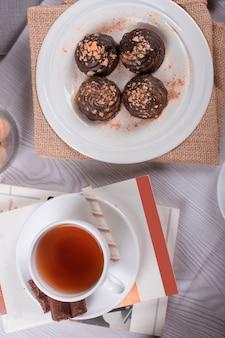 Buch, tasse tee und schokolade auf dem tisch
