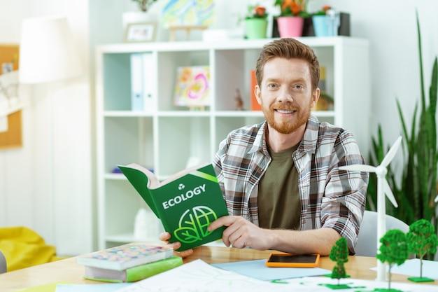 Buch über ökologie. lächelnder gutaussehender rothaariger typ, der ein kariertes hemd trägt und ein ökologisches tutorial inspiziert