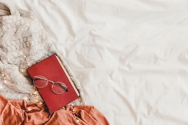 Buch und brille auf dem bett