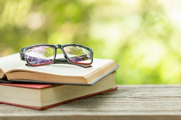 Buch und brille auf holztisch mit abstrakter grüner natur verschwimmen lese- und bildungskonzept