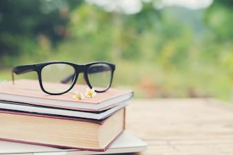 Buch und Brille zum Lesen und Schreiben über verschwommenes Natur outd