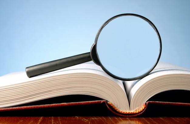 Buch und eine lupe auf einem blauen hintergrund