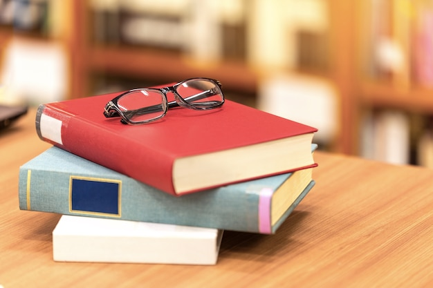 Buch und gläser auf tabelle in der bibliothek.