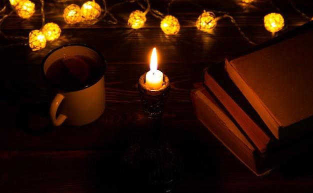 Buch und heißer teebecher für gemütliche abende. urlaubsstimmungsfoto mit weihnachtsbeleuchtung. holzherz und kerze. hygge-konzept. perfekte herbstflachlage.