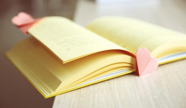 Buch- und herzförmige lesezeichen auf einem holztisch