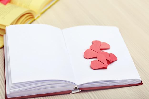 Buch- und herzförmige lesezeichen auf holzuntergrund