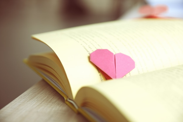 Buch und herzförmiges lesezeichen auf einem holztisch