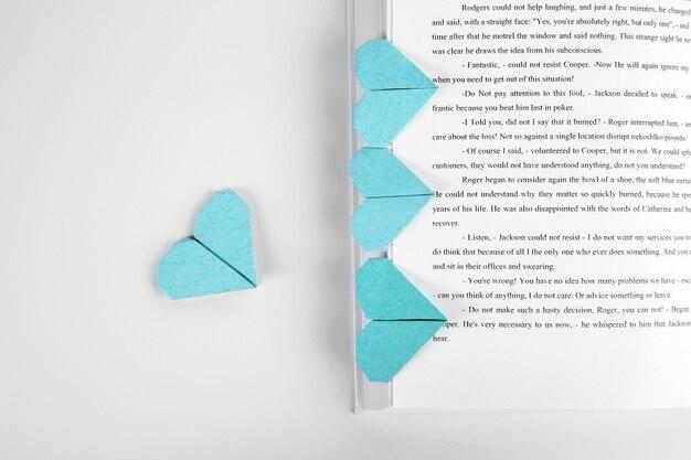 Buch und herzförmiges lesezeichen auf hellem holzhintergrund