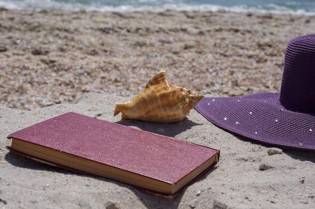 Buch und hut am strand