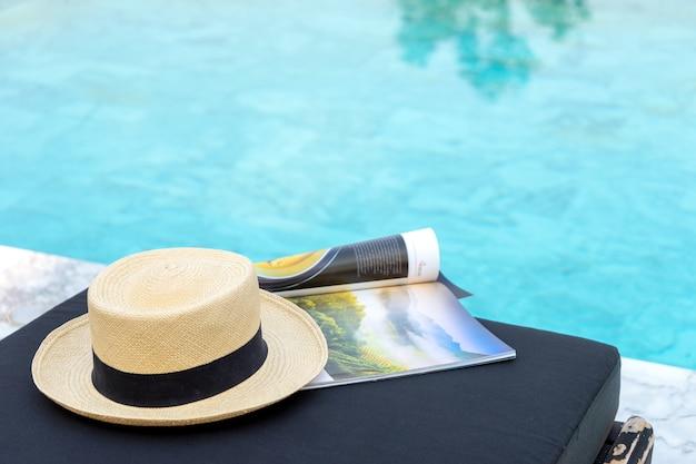 Buch und hut auf der sonnenliege am pool,