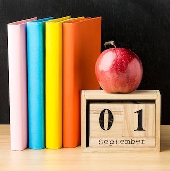 Buch und kalender mit apfel für den schulanfang