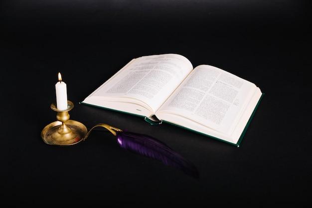 Buch und leuchter auf schwarz