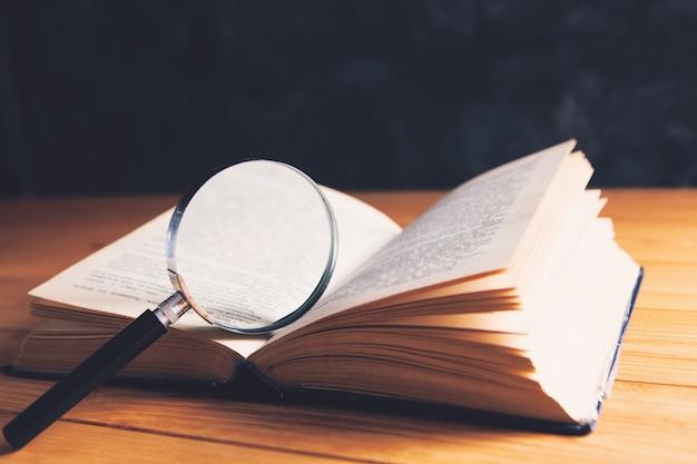 Buch und lupe auf dem tisch. such- und studienkonzept