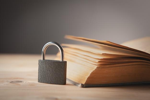Buch und schloss auf einem holztisch, verstecktes wissen