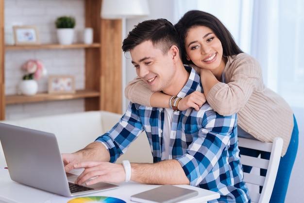 Buche online. glückliche attraktive frau, die mann umarmt, während er laptop benutzt