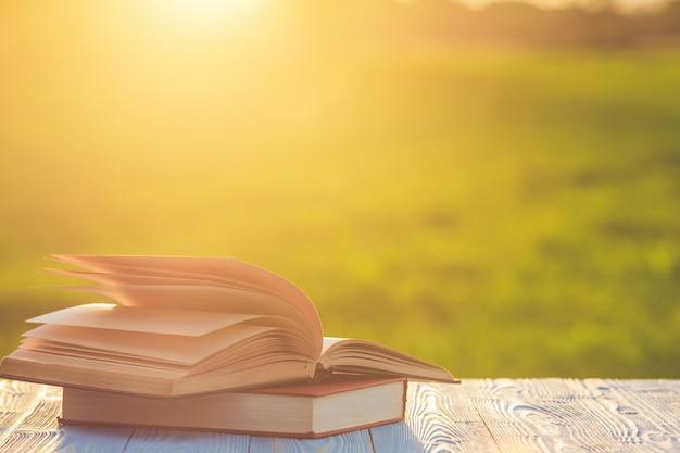 Buchen sie auf holztisch mit abstrakter unschärfe und bokeh in der sonnenaufgang- oder sonnenuntergangzeit