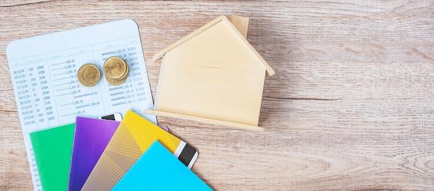 Buchen sie bank mit hausmodell und schlüssel auf hölzerner tabelle mit kopienraum. finanz-, geld-, refinanzierungs-, immobilien- und neues honekonzept