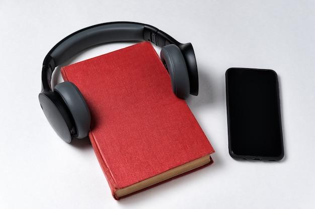 Buchen sie mit kopfhörern neben dem handy. konzept für hörbücher. weißer hintergrund, kopienraum.