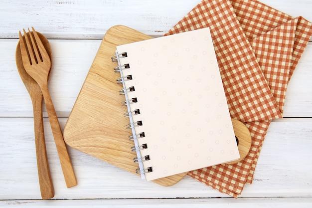 Buchen sie notizblockpapier auf dem hacken des schneidebretts und der tischdecke auf weißer tabelle, ein rezeptlebensmittel für schussanmerkung der gesunden gewohnheiten