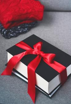 Buchgeschenke verziert mit rotem band, winter hugge saisonkonzept, cristmas feiertagsgeschenke