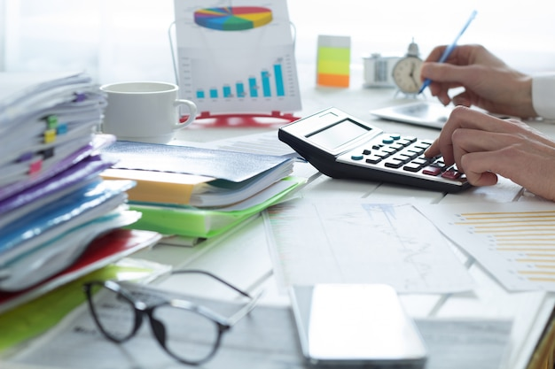 Buchhalter auf einem taschenrechner, der einen finanzbericht macht. steuerzeit