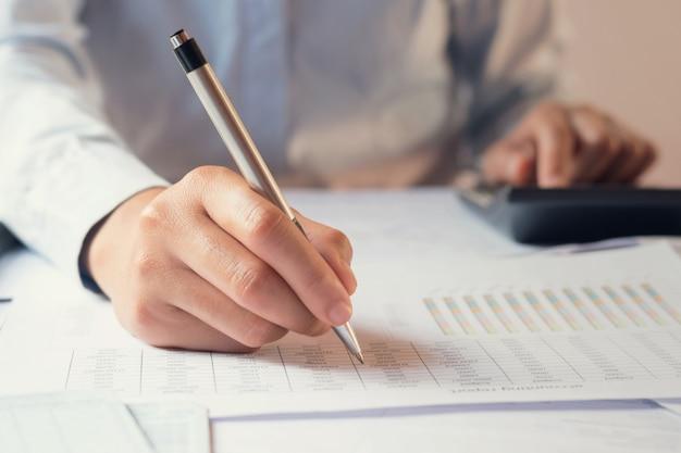 Buchhalter, der an schreibtisch arbeitet, um taschenrechner mit buchhalter arbeitend auf schreibtisch zu verwenden