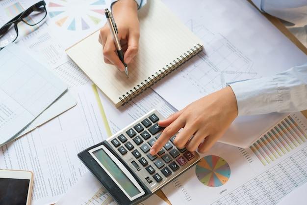 Buchhalter, der an schreibtisch arbeitet, um taschenrechner mit stift auf buch zu verwenden. konzeptfinanzierung