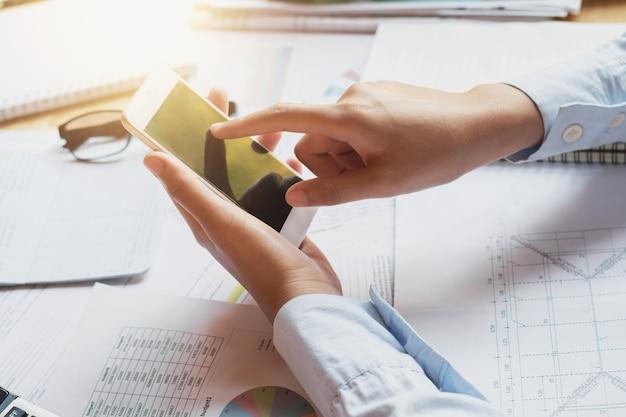 Buchhalter, der an schreibtisch mit smartphone arbeitet