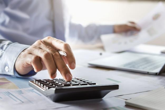 Buchhalter, der an schreibtisch unter verwendung des kalkulators arbeitet, um finanzbericht im büro zu berechnen