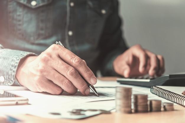 Buchhalter, der den stift und taschenrechner arbeiten mit dokument im büro verwendet