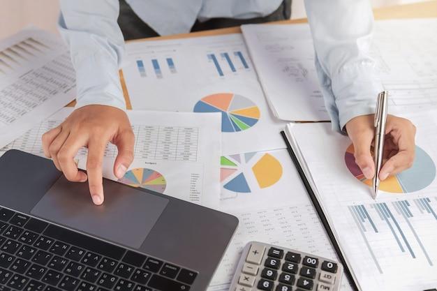 Buchhalter, der laptop mit stift auf schreibtisch im büro verwendet. finanz- und rechnungswesenkonzept
