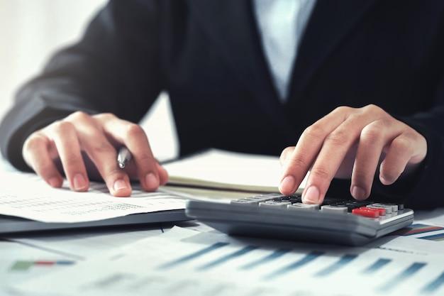 Buchhalter, der taschenrechner für die berechnung mit dem laptop arbeitet im büro verwendet