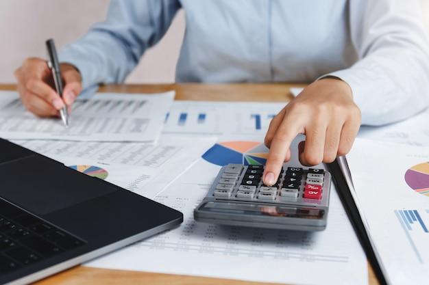 Buchhalter, der taschenrechner mit stift auf schreibtisch für berechnet finanzierung dat verwendet