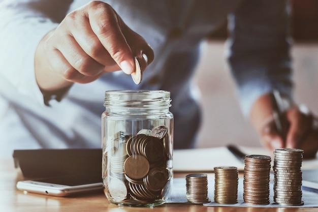 Buchhaltereinsparungsgeldhand, welche die münzen sich setzen in krugglas hält
