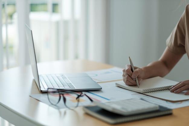 Buchhalterfrau, die prüfung und berechnung der kosten für den jahresfinanzbericht bilanzausweis arbeitet, finanzen macht notizen zum papierprüfdokument.