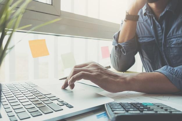 Buchhalterhand, die bleistift hält, der am rechner arbeitet, um finanzdatenbericht zu berechnen