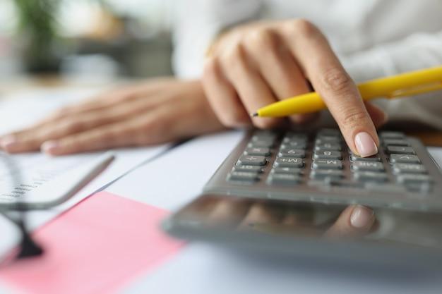 Buchhalterhand, die tasten auf taschenrechner am tisch mit dokumentennahaufnahme drückt