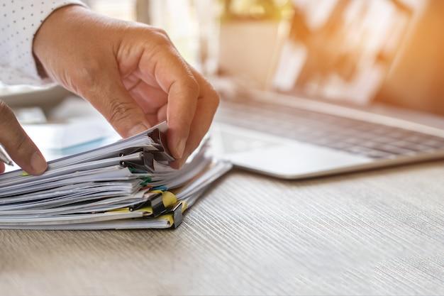 Buchhalterhandgebrauch berechnen den finanzbericht und zählen taschenrechner für die prüfung von dokumenten