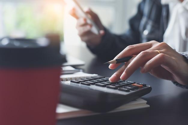 Buchhalterin mit taschenrechner während der arbeit im büro