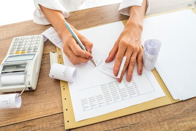 Buchhalterin oder finanzberaterin prüft und vergleicht quittungen und statistische daten, während sie einen abschlussbericht erstellt und an ihrem schreibtisch mit einer zusätzlichen maschine arbeitet.