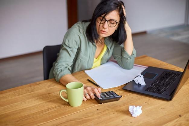Buchhalterin sitzt auf taschenrechner am holztisch, moderner arbeitsplatz, freiberufler, der zu hause arbeitet. frauen, die beschäftigt sind, verwalten die ausgaben für das familienbudget.