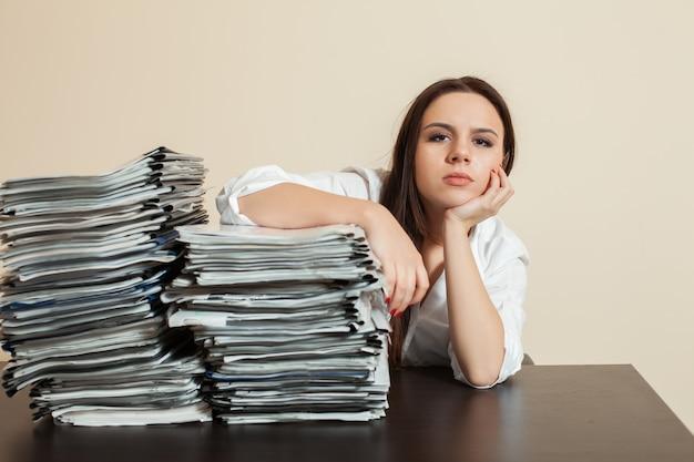 Buchhalterin umarmt große stapel von dokumenten