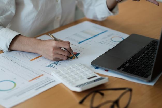 Buchhalterin verwendet rechner und computeranalytischen marketingbericht über holzschreibtisch im büro. finanz- und rechnungswesen-konzept.