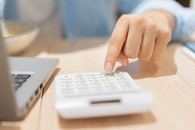 Buchhaltungsmannhand, die auf rechner drückt, um den monatlichen gewinn des geschäfts zu berechnen