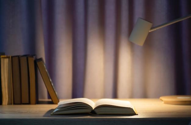 Buchhintergrund. offenes buch auf einem tisch in einem universitäts- oder heimschreibtisch und einer schulbibliothek. lesen, literatur, studium und wissenskonzept. foto in hoher qualität