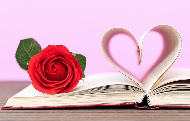 Buchseiten in herzform und rote rose gebogen. liebeskonzept der herzform von den buchseiten auf rosa hintergrund