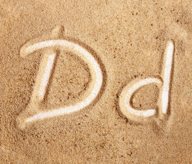 Buchstabe d englisches handgeschriebenes alphabet im sand